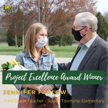 Superintendent Power hands flowers to teacher