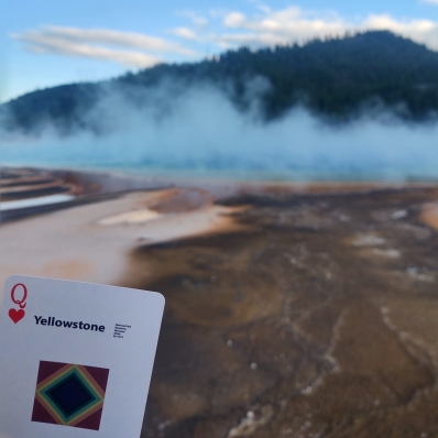 playing card in front of a geyser at Yellowstone