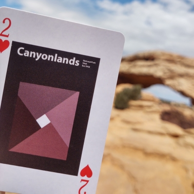 playing card in front of a rock archway at Canyonlands National Park