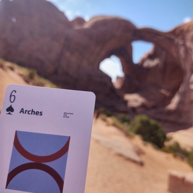 playing card in front of a rock archway at Arches National Park