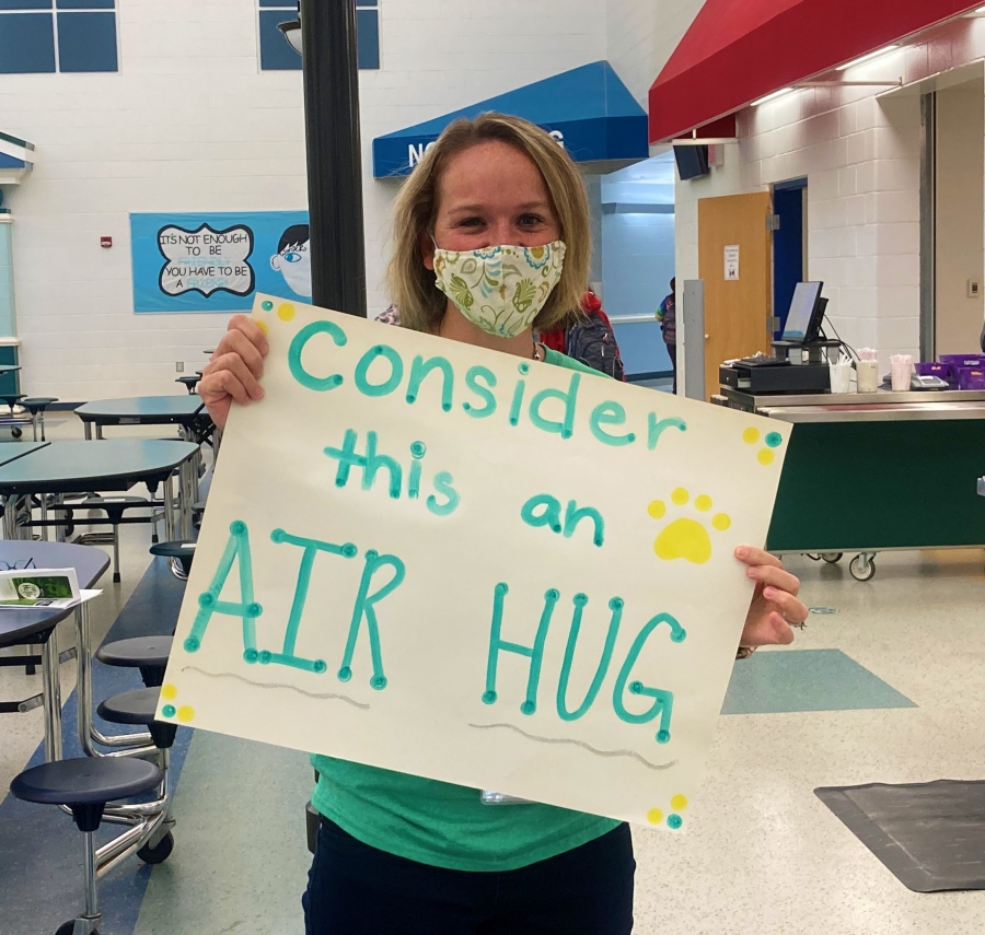 LMIS Staff member with a sign that reads: Consider this an air hug!